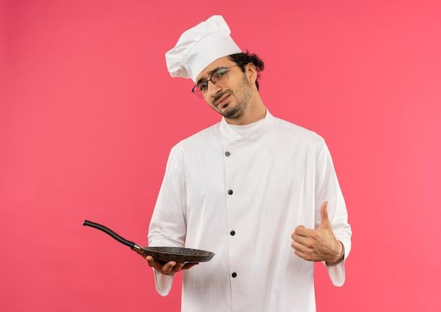 Onaangename jonge mannelijke kok die eenvormige chef-kok en glazen draagt die koekenpan zijn duim omhoog houden die op roze muur wordt geïsoleerd