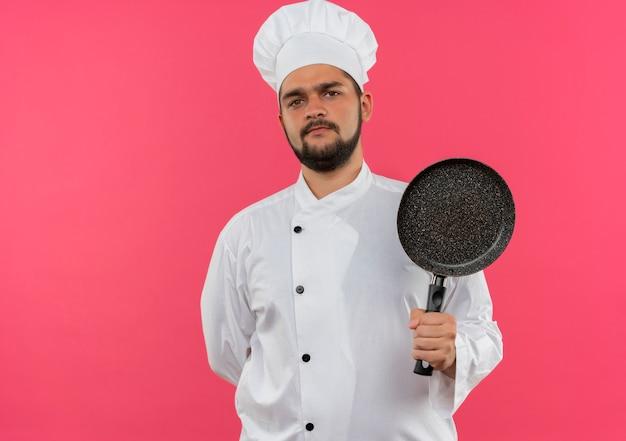 Onaangename jonge mannelijke kok in de pan van de chef-kok de eenvormige holding met één hand achter rug geïsoleerd op roze ruimte