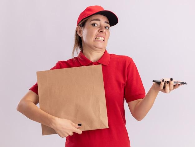 Onaangename jonge mooie bezorgvrouw in uniform houdt papieren pakket en telefoon geïsoleerd op een witte muur