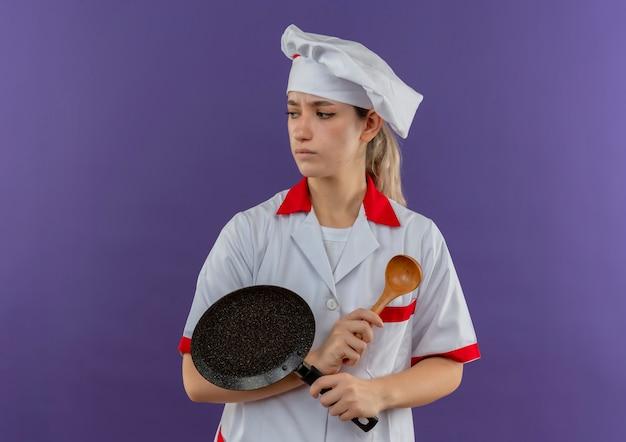 Onaangename jonge mooie kok in de koekenpan en de lepel van de chef-kok de eenvormige holding die kant bekijken die op purpere ruimte wordt geïsoleerd