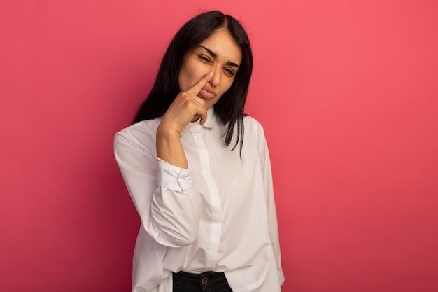 Onaangename jonge mooie vrouw die wit t-shirt draagt dat vinger op neus zet
