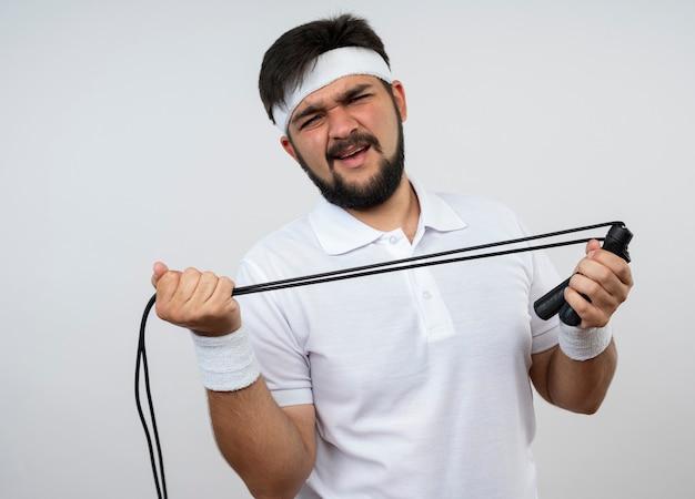 Onaangename jonge sportieve man met hoofdband en polsband die een springtouw uitrekt geïsoleerd op een witte muur