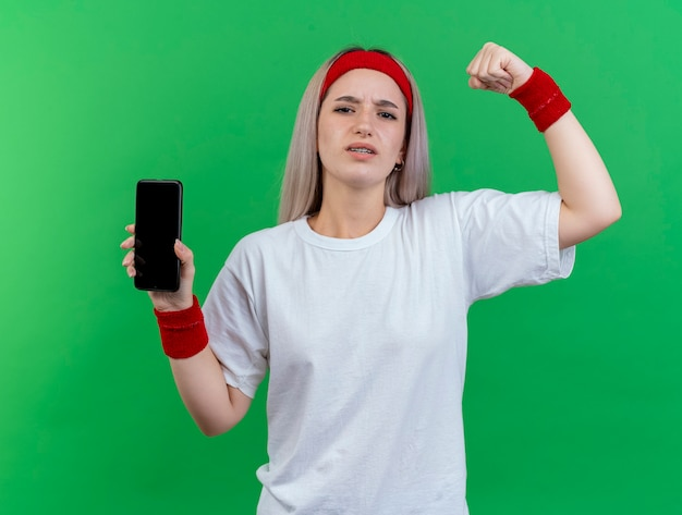 Onaangename jonge sportieve vrouw met beugels die hoofdband en polsbandjes dragen staat met opgeheven vuist omhoog en houdt telefoon geïsoleerd op groene muur