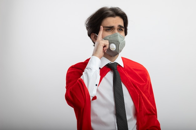 Onaangename jonge superheld kerel kijken kant dragen stropdas en medisch masker vinger op tempel