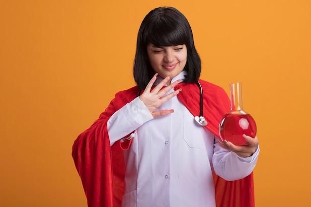 Onaangename jonge superheld meisje dragen stethoscoop met medische gewaad en mantel houden en kijken naar chemie glazen fles gevuld met rode vloeistof geïsoleerd op oranje
