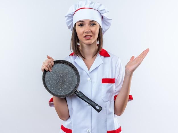 Onaangename jonge vrouwelijke kok in uniform van de chef-kok die een koekenpan vasthoudt die de hand uitspreidt op een witte muur