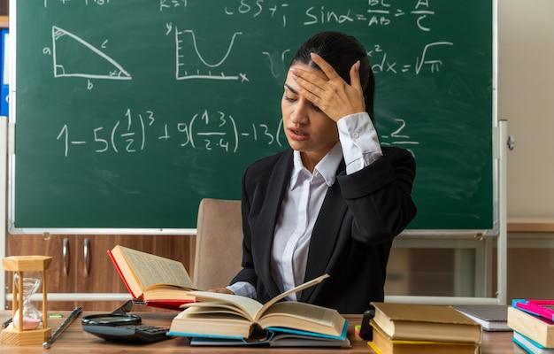 Onaangename jonge vrouwelijke leraar zit aan tafel met schoolbenodigdheden die een boek lezen en hand op het hoofd zetten in de klas