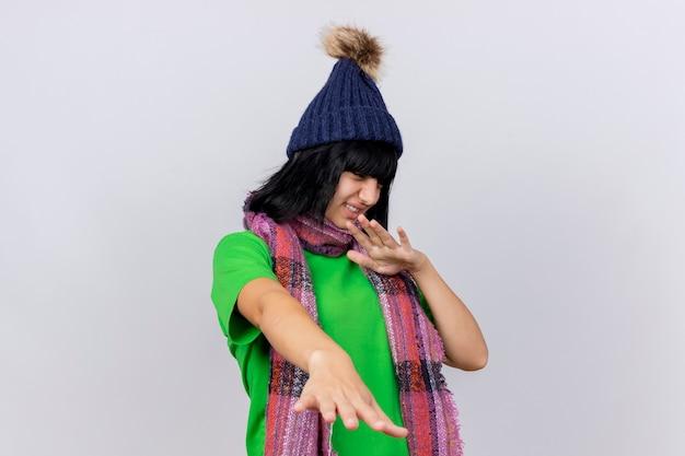 Onaangename jonge zieke kaukasische meisje dragen winter hoed en sjaal handen uitstrekken naar camera doet geen gebaar kijken kant geïsoleerd op een witte achtergrond met kopie ruimte
