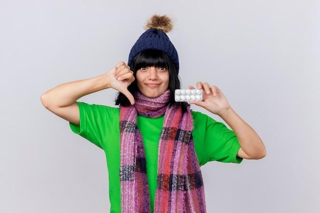 Onaangename jonge zieke kaukasische meisje dragen winter muts en sjaal kijken camera weergegeven: pak tabletten en duim omlaag geïsoleerd op een witte achtergrond met kopie ruimte