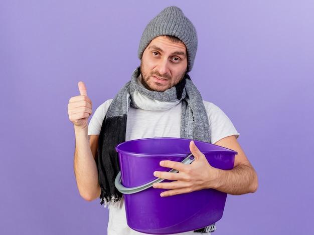 Onaangename jonge zieke man die de wintermuts met sjaal draagt die plastic emmer houdt en duim toont die op paars wordt geïsoleerd