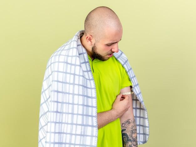 Onaangename jonge zieke man gewikkeld in geruite ruimen en maatregelen temperatuur met thermometer geïsoleerd op olijfgroene muur