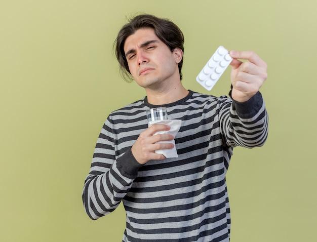 Onaangename jonge zieke man met glas water en pillen standhouden op camera geïsoleerd op olijfgroene achtergrond