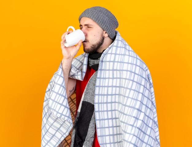 Onaangename jonge zieke man met muts en sjaal verpakt in plaid drinken kopje thee geïsoleerd op oranje muur