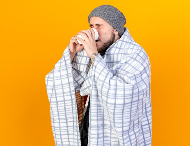 Onaangename jonge zieke man met muts en sjaal verpakt in plaid drinkt kopje thee geïsoleerd op oranje muur