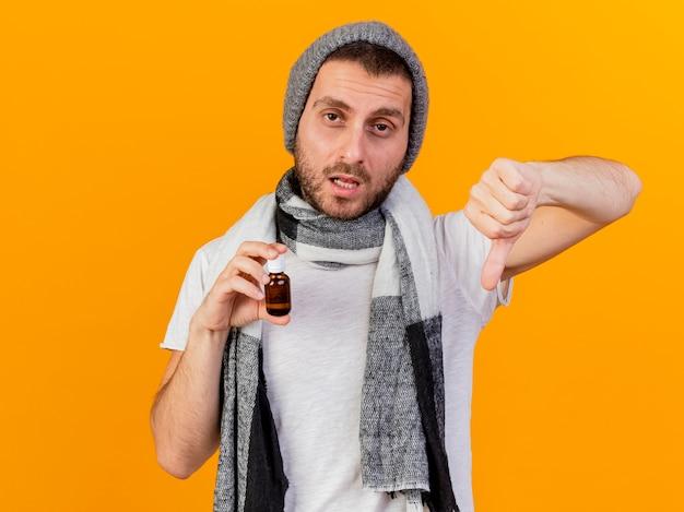 Onaangename jonge zieke man met winter hoed en sjaal met geneeskunde in glazen fles met duim omlaag geïsoleerd op gele achtergrond