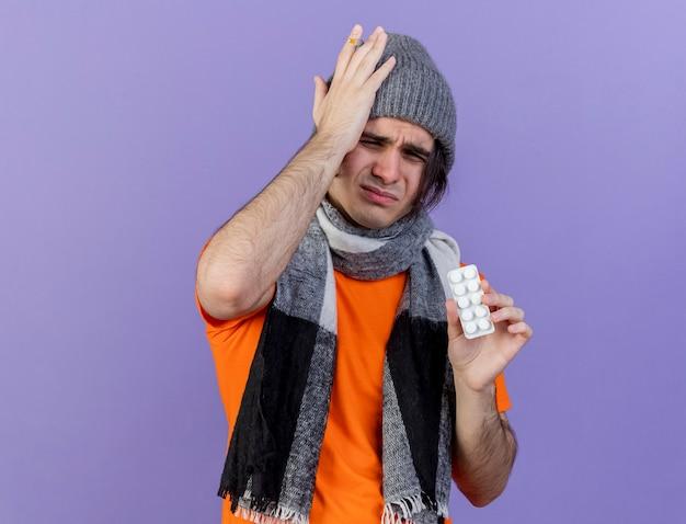 Onaangename jonge zieke man met winter hoed met sjaal houden pillen hand zetten pijnlijke hoofd geïsoleerd op paarse achtergrond