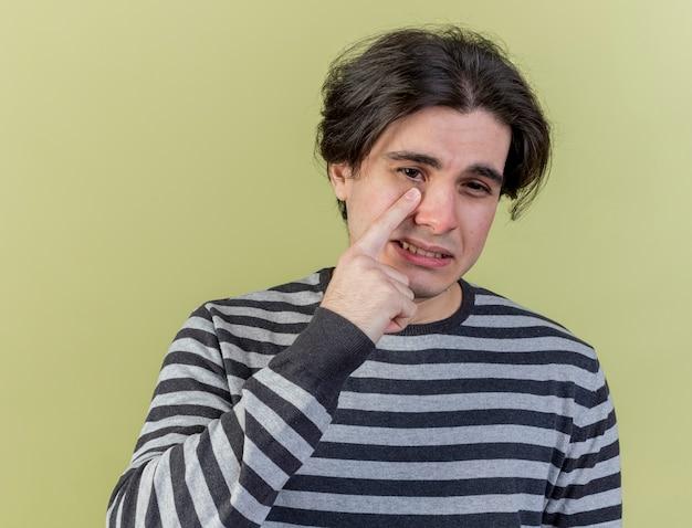 Onaangename jonge zieke man vinger op oog zetten geïsoleerd op olijfgroene achtergrond