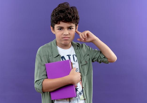Onaangename kleine schooljongen die boeken houdt en vinger op oor zet dat op purpere muur wordt geïsoleerd