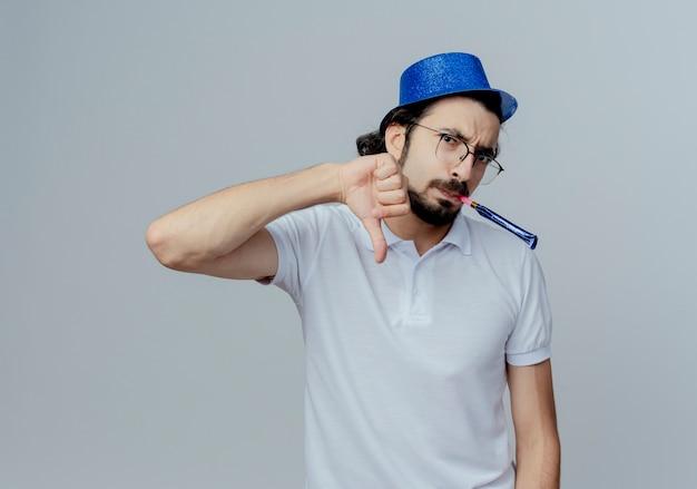 Onaangename knappe man met bril en blauwe hoed blaast zijn duim omlaag geïsoleerd op wit