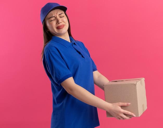 Onaangename mooie bezorger in uniform houdt zware kartonnen doos op roze