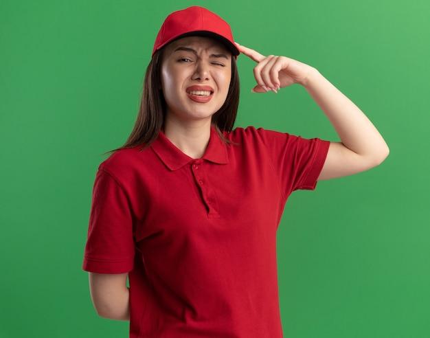 Onaangename mooie bezorger in uniform legt de vinger op het hoofd op groen