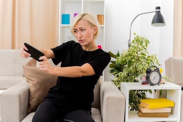 Onaangename mooie blonde russische vrouw zit op fauteuil te houden en te kijken naar telefoon in de woonkamer