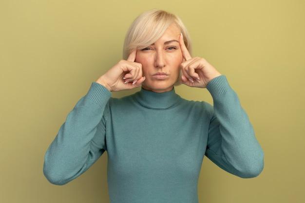 Onaangename mooie blonde slavische vrouw legt vingers op slapen op olijfgroen