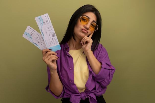 Onaangename mooie brunette vrouw in zonnebril legt vinger op gezicht en houdt vliegtickets geïsoleerd op olijfgroene muur