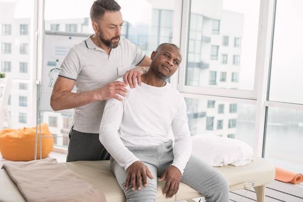 Onaangename pijn. trieste jonge ongelukkige man die een dokter bezoekt terwijl hij klaagt over de pijn in de schouder