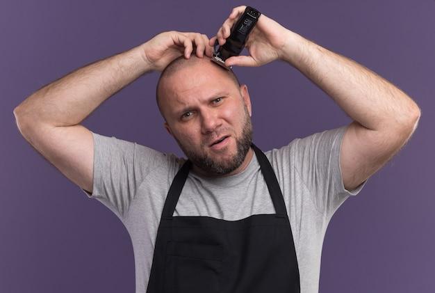 Onaangename slavische mannelijke kapper van middelbare leeftijd in uniform haar knippen met tondeuse geïsoleerd op paarse muur
