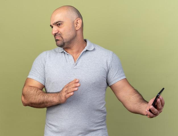 Onaangename, toevallige man van middelbare leeftijd die een mobiele telefoon vasthoudt en een weigeringsgebaar doet, kijkend naar de zijkant geïsoleerd op de olijfgroene muur