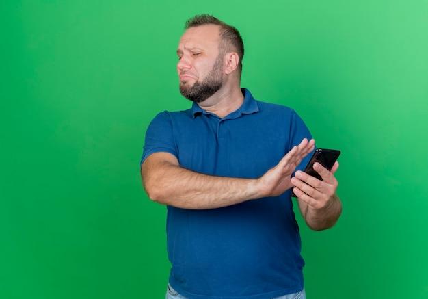 Onaangename volwassen slavische man die mobiele telefoon houdt en geen gebaar doet met hand geïsoleerd op groene muur met kopie ruimte