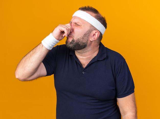 Onaangename volwassen slavische sportieve man met hoofdband en polsbandjes die zijn neus sluiten geïsoleerd op oranje muur met kopie ruimte