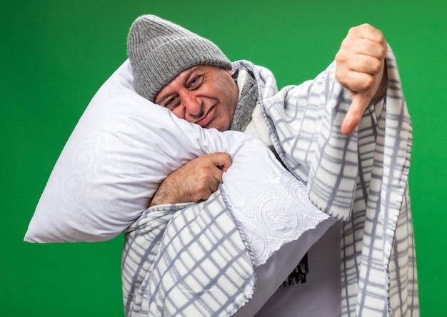 Onaangename volwassen zieke blanke man met sjaal om de nek met wintermuts gewikkeld in geruite duimen naar beneden vasthouden en hoofd op kussen geïsoleerd op groene muur met kopie ruimte