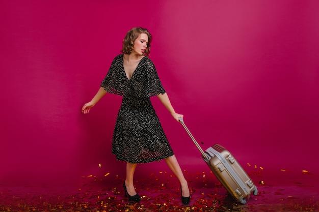 Onaangename vrouw in zwarte jurk met zware koffer. indoor portret van prachtig meisje met vermoeide gezichtsuitdrukking poseren met bagage.