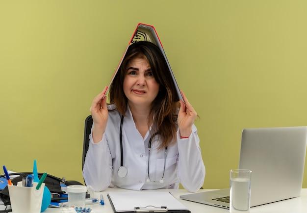 Onaangename vrouwelijke arts van middelbare leeftijd die medische mantel en stethoscoop draagt ?? die aan bureau zit met medische hulpmiddelen en laptop met map op hoofd geïsoleerd