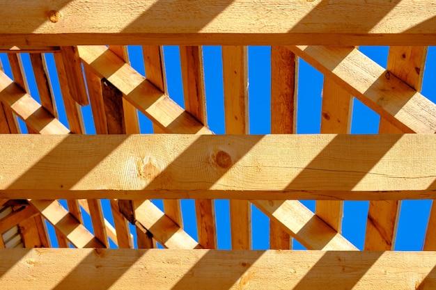 Onafgewerkt houten dak tegen de blauwe lucht