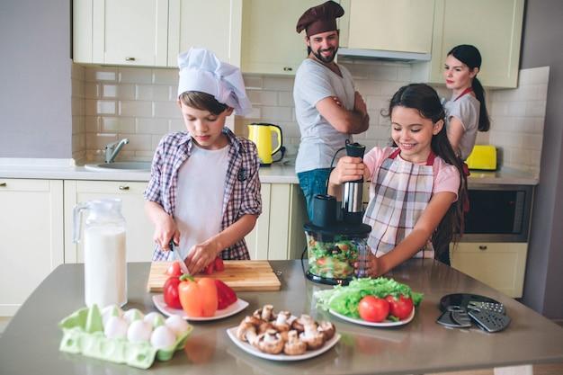 Onafhankelijke kinderen bereiden samen salade zonder ouders. het meisje mengt groenten in mixer terwijl de jongen stukken tomaten snijdt. ouders kijken ernaar en controleren.