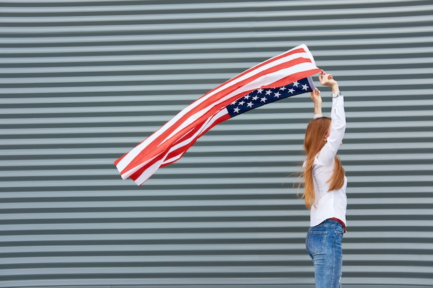 Onafhankelijkheidsdag en patriottisch concept. jonge roodharigevrouw met rode geschilderde lippen die zich met gegolfd door de vlag van de windv.s. bevinden, die het hierboven houden. grijs metalen paneel.