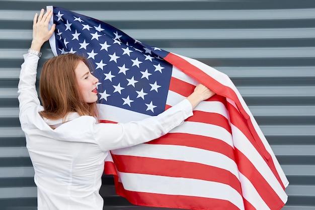 Onafhankelijkheidsdag en patriottisch concept. jonge roodharigevrouw met rode geschilderde lippen die zich met gegolfd door de vlag van de windv.s. bevinden
