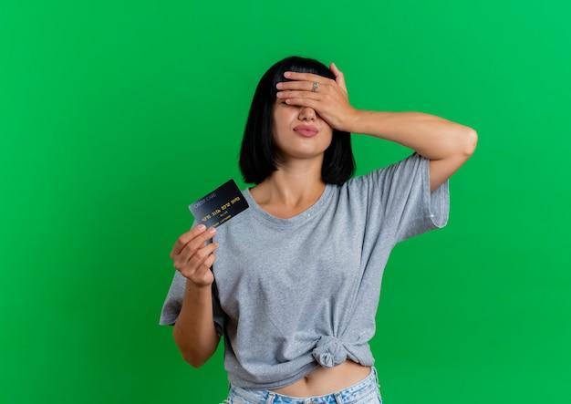 Onbehaagd jong donkerbruin kaukasisch meisje houdt creditcard en sluit ogen met hand die op groene achtergrond met exemplaarruimte wordt geïsoleerd