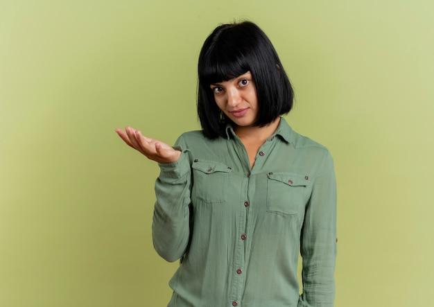 Onbehaagd jong donkerbruin kaukasisch meisje houdt hand open geïsoleerd op olijfgroene achtergrond met exemplaarruimte