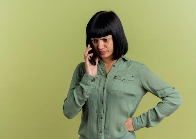 Onbehaagd jong donkerbruin kaukasisch meisje legt hand op taille die op telefoon spreekt