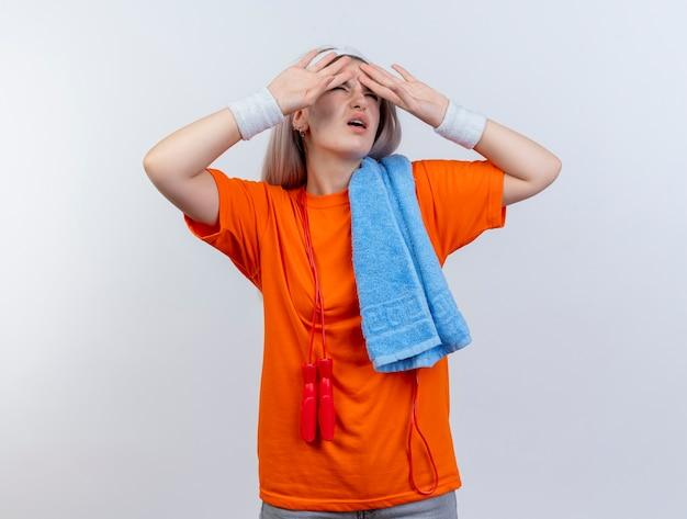 Onbehaagd jong kaukasisch sportief meisje met beugels en met touwtjespringen om de nek dragen van hoofdband en polsbandjes met handdoek op schouder legt handen op voorhoofd op witte muur