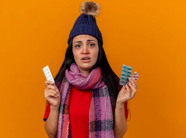 Onbehaagd jong kaukasisch ziek meisje die de winterhoed en sjaal dragen die pakken medische pillen houden die op oranje muur met exemplaarruimte worden geïsoleerd