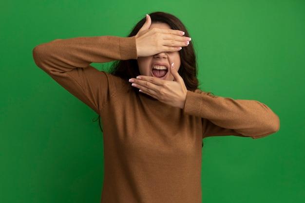 Onbehaagd jong mooi meisje bedekt gezicht met handen geïsoleerd op groene muur