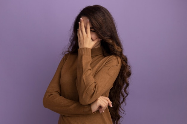 Onbehaagd jong mooi meisje dat een bruin coltrui draagt ?? die gezicht met hand draagt dat op purpere muur wordt geïsoleerd