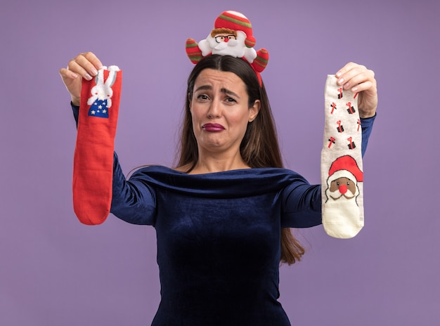 Onbehaagd jong mooi meisje die blauwe kleding en de hoepel van het kerstmishaar dragen die kerstmissokken stak bij camera die op purpere achtergrond wordt geïsoleerd