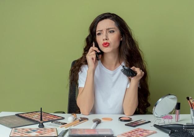 Onbehaagd jong mooi meisje zittend aan make-up tafel met make-up tools kam houden en praten over de telefoon kijken kant geïsoleerd op olijfgroene achtergrond