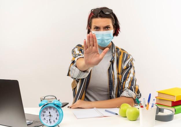 Onbehaagd jong studentenmeisje met bril op hoofd en masker zittend aan een bureau met universitaire hulpmiddelen gebaren stop bij camera geïsoleerd op een witte achtergrond